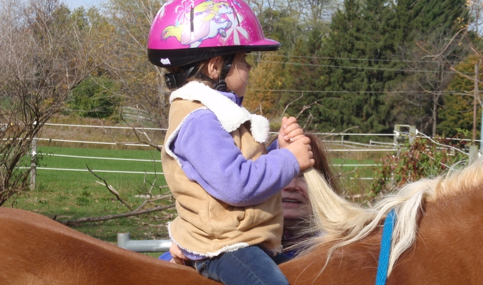 Young girl the mane as she sits on a horse.