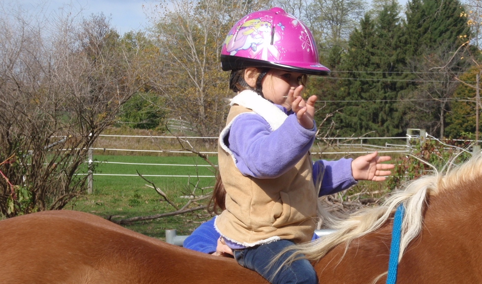 Young girl letting go of the mane as she rides a large horse